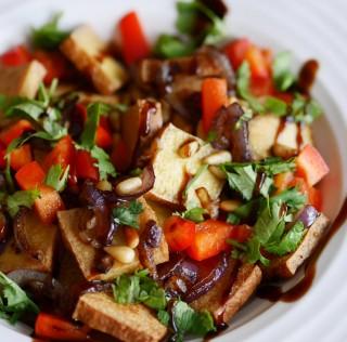 Salade tiède de tofu fumé, poivrons croquants, oignons caramélisés et pignons grillés